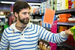 Homme sélectionnant un produit d'épicerie d'étagère Photo stock