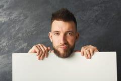 Homme sérieux bel tenant le livre blanc dans le studio Photos libres de droits