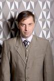 Homme sérieux d'affaires se tenant près du mur - photo courante Image libre de droits