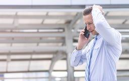 Homme sérieux d'affaires utilisant le téléphone portable extérieur photographie stock