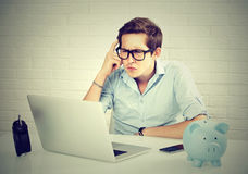 Homme sérieux dans la chemise bleue regardant l'ordinateur portable tout en se reposant à son lieu de travail photos libres de droits