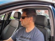 Homme sérieux dans la fenêtre de voiture photographie stock libre de droits