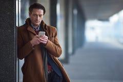Homme sérieux introduisant au clavier le téléphone images libres de droits