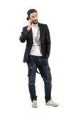 Homme sérieux parlant sur le chapeau de port de téléphone portable vers l'arrière Photos stock