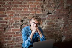 Homme sérieux pensant au nouveau plan d'action, se reposant avec l'ordinateur portable photographie stock