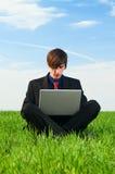Homme sérieux s'asseyant avec l'ordinateur Photo libre de droits