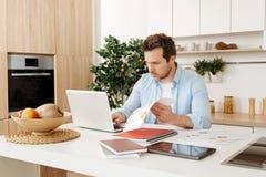 Homme sérieux semblant travaillant sur un ordinateur portable et vérifiant des documents Photographie stock