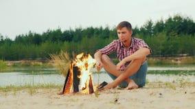 Homme sérieux solitaire s'asseyant par le feu de camp, guimauves de rôti sur un bâton banque de vidéos