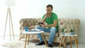 Homme sérieux sur le sofa avec le comprimé numérique utilisant le journal intime banque de vidéos