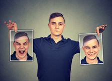 Homme sérieux tenant deux masques différents d'émotion de visage de se image stock
