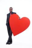 Homme sérieux tenant le grand coeur, symbole de l'amour Images libres de droits