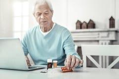 Homme sérieux triste regardant les pilules et à l'aide de l'ordinateur portable Image stock