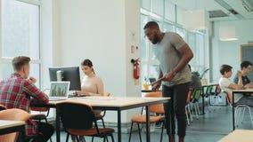 Homme sérieux venant dans l'espace coworking Planification d'homme de couleur à travailler dans l'espace ouvert banque de vidéos