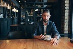 Homme sûr appréciant une tasse de café tout en prenant le déjeuner pause en à l'intérieur café semblant songeur photo stock