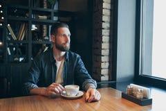 Homme sûr appréciant une tasse de café tout en prenant le déjeuner pause en à l'intérieur café semblant songeur photographie stock