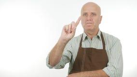 Homme sûr avec le signe d'attention de tablier gestes de main d'avertissement photos stock