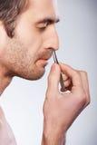Homme s'épilant des cheveux de nez. photographie stock libre de droits
