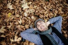 Homme s'étendant sur des lames d'automne. Photos libres de droits