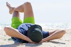 Homme s'étendant sur son dos sur la plage photographie stock libre de droits