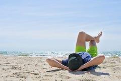 Homme s'étendant sur son dos sur la plage photos stock