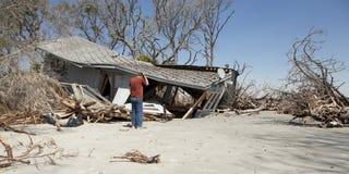 Homme s'affligeant au-dessus de la maison détruite photos stock