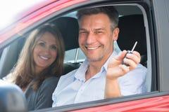 Homme s'asseyant à l'intérieur de la voiture montrant la clé de voiture Photo stock