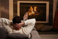 Homme s'asseyant à la cheminée photos libres de droits