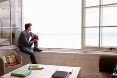 Homme s'asseyant à la fenêtre et regardant la belle vue de plage Photographie stock libre de droits