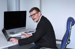 Homme s'asseyant au bureau Photo stock