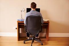 Homme s'asseyant au bureau fonctionnant à l'ordinateur dans le siège social photos libres de droits