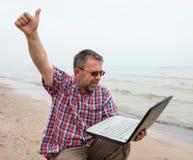 Homme s'asseyant avec l'ordinateur portable Photographie stock libre de droits