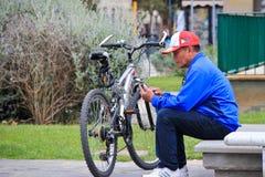 Homme s'asseyant avec la bicyclette Images stock