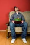 Homme s'asseyant avec le cadeau Photo stock
