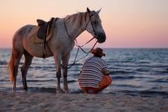 Homme s'asseyant avec le cheval debout sur la plage par la mer au coucher du soleil Photographie stock