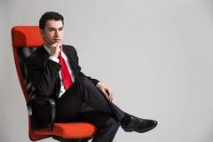 Homme s'asseyant avec les pattes croisées images stock