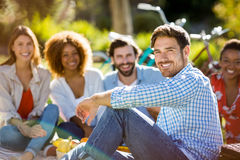 Homme s'asseyant avec ses amis en parc Photographie stock