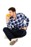 Homme s'asseyant avec une orange Image stock