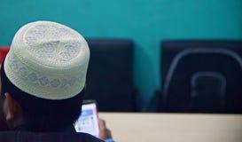 Homme s'asseyant dans des chapeaux blancs de port d'un endroit images stock