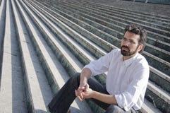 Homme s'asseyant dans des escaliers Image stock