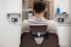 Homme s'asseyant dans la chaise au raseur-coiffeur ou au salon de coiffure photo libre de droits