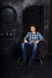 Homme s'asseyant dans la chaise de dos de haute dans l'arrangement mystérieux Photographie stock libre de droits