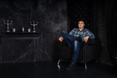 Homme s'asseyant dans la chaise de dos de haute dans la Chambre hantée Image stock