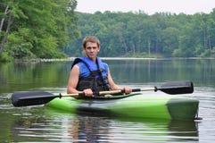 Homme s'asseyant dans le kayak Image stock