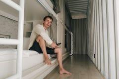 Homme s'asseyant dans une chambre à coucher élégante de pension photos stock