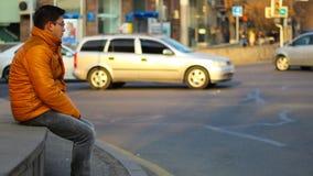 Homme s'asseyant dans une veste orange avec le regard réfléchi, sur le fond des voitures de laps de temps dans la ville banque de vidéos