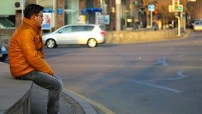 Homme s'asseyant dans une veste orange avec le regard réfléchi, sur le fond des voitures de laps de temps dans la ville vidéo de  banque de vidéos