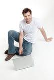 Homme s'asseyant derrière le sourire d'ordinateur portatif de blanck Photographie stock