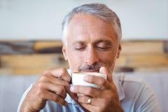 Homme s'asseyant en café ayant le café Images stock