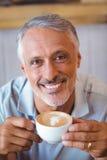 Homme s'asseyant en café ayant le café Photos stock