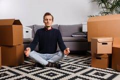 Homme s'asseyant en position de lotus sur le tapis sur le fond des boîtes en carton, sofa gris photos stock